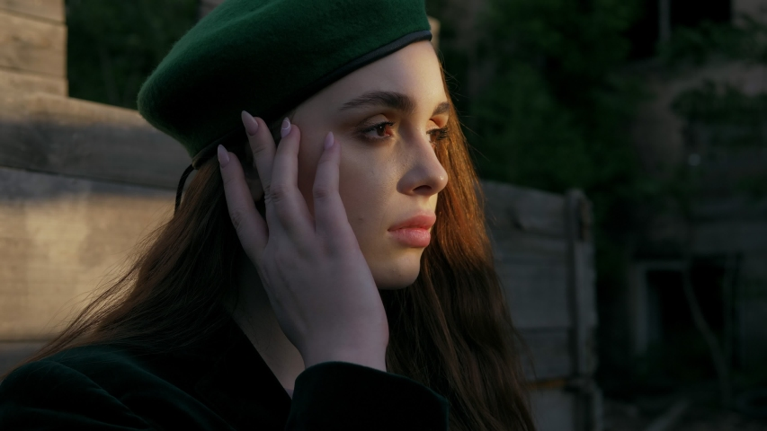Beautiful young woman in vintage clothes and green beret holds hands near face and poses extreme close view | Shutterstock HD Video #1031222768