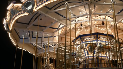 Illuminated merry go round in park. Brightly illuminated roundabout spinning in wonderful amusement park at night.