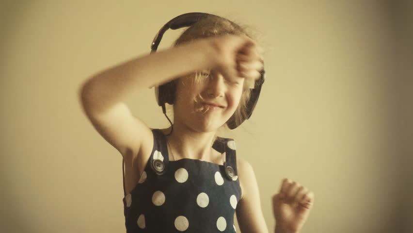 Happy little girl dancing in headphones. Slow motion. | Shutterstock HD Video #10312268