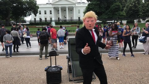 Recorded in Washington, D.C. (U.S.A) on June 7, 2019.  A Donald Trump Impersonator wearing a mask performs in front of the White House for tourists passing by.