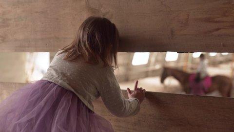 Toddler sneak peeking with her mom at a horse training arena, medium shot