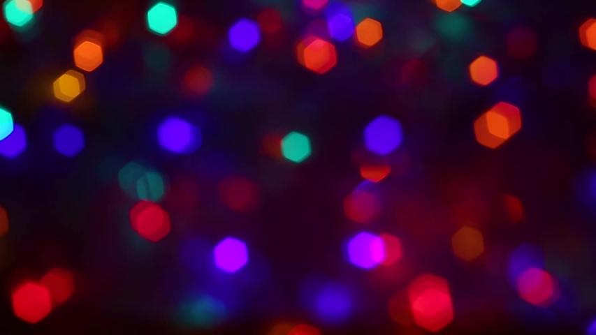 Beautiful vivid multicolor holiday background of defocused shiny decorations isolated on black backdrop. Christmas, xmas, new year party celebration time.