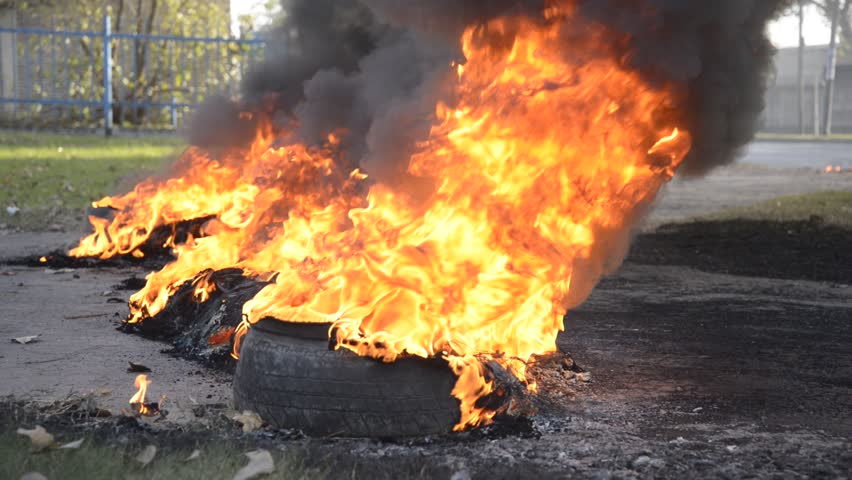 Flames and smoke emanating  from tires on fire on the street during a labor strike and protest at Rosario city, Argentina