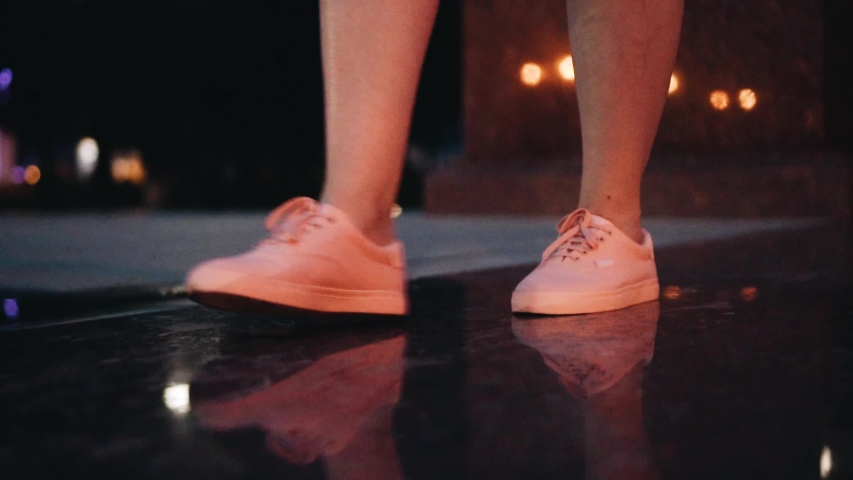 Close-up of women's feet in pink sneakers. In motion. The girl goes through the city at night. beautiful light and reflection on wet surface   Shutterstock HD Video #1031477078