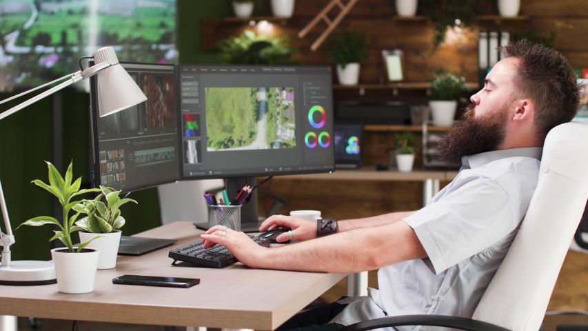 Video editor working in professional software. He uses a dual screen setup and works in modern designed studio office