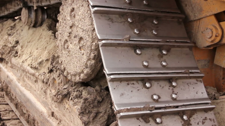 Close up view on bulldozer's undercarriage during pushing ground at construction site. | Shutterstock HD Video #1031539778