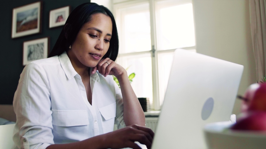 Young asian woman with laptop sitting at the desk indoors at home, typing. | Shutterstock HD Video #1031601038