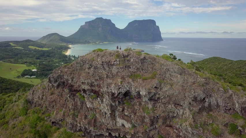 Aerial: A Couple Hiking Down a Rock Looking Out to the Tasman Sea in Lord Howe Island, Australia #1031653808