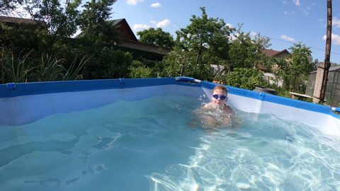 Boy swims in pool under water. Swimming glasses. guy is blond or red. Waves and air bubbles under water. Clear clear water in pool. Turquoise wave.  Boy dives into depths. Sunny summer day. Blue sky