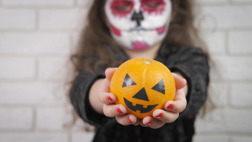 Halloween kid. A little girl holds in her hands an evil pumpkin. | Shutterstock HD Video #1031699018
