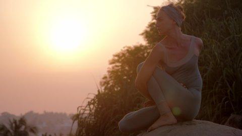 yoga practitioner does matsyendrasana asana on huge stone at bright sunrise light low angle shot slow motion. Concept fitness yoga healthy lifestyle