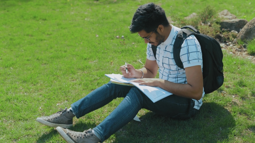 Student with Glasses and Backpack Doing Homework Sitting on the Lawn in the City Park #1031862218