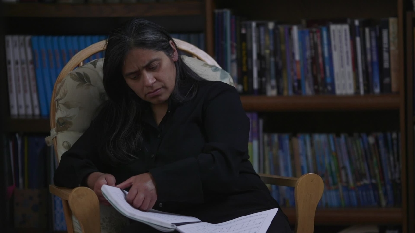 Hispanic Woman Sitting on Rocking Chair Reviewing Material | Shutterstock HD Video #1031885438
