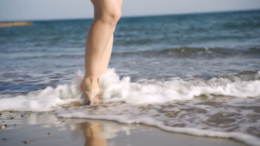 Close up shot of the feet of a woman who walks barefoot on wet sand | Shutterstock HD Video #1031899508