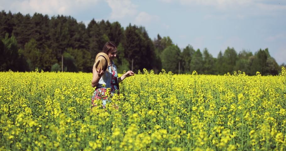 An attractive woman walks in a yellow rapeseed field. Pretty female model resting outdoors. Beautiful summer landscape. #1031970338