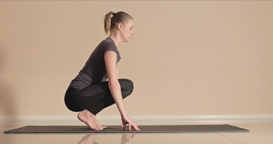 Yoga fail as a young female instructor attempts the crane or crow pose and falls down and laughs then her class throws pillows at her jokingly from off screen   Shutterstock HD Video #1032027038