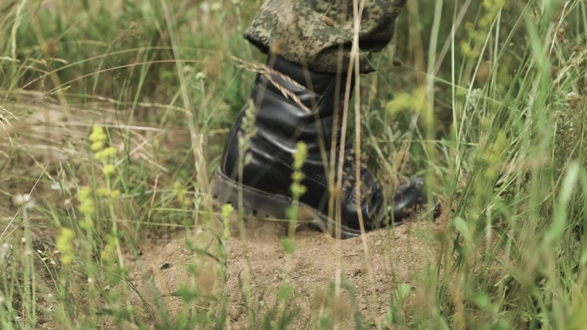 Soldiers walking on the ground, the wasteland and the steppe, the view of the feet in military boots. | Shutterstock HD Video #1032046808