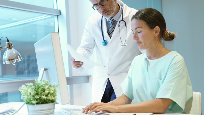 Doctor and nurse discussing patient results in hospital office | Shutterstock HD Video #1032057008