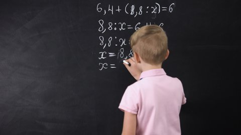 Boy writing on chalkboard math equation, solving exercise, education reform