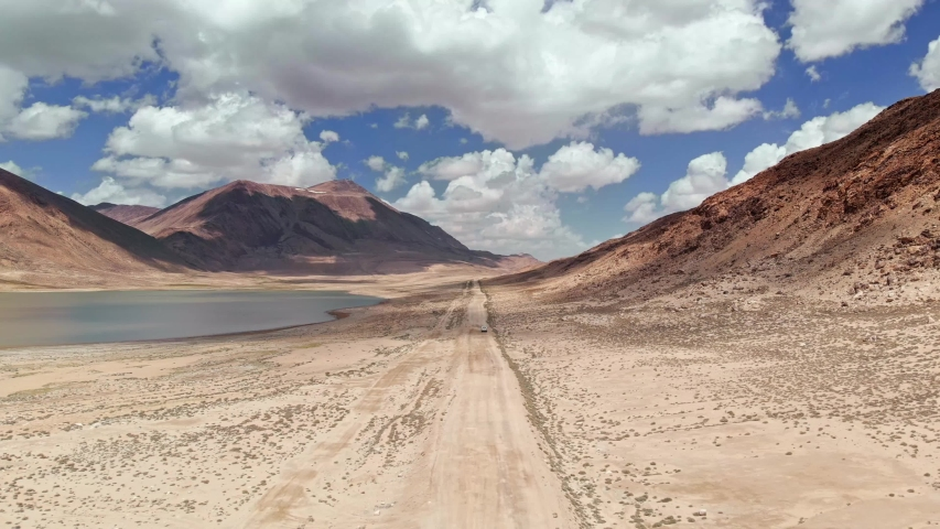 Aerial over off road 4x4 car driving along gravel trail path near arid desert mountains.Pamir Highway silk road trip adventure in Kyrgyzstan and Tajikistan desert,central Asia.4k drone flight video | Shutterstock HD Video #1032277238