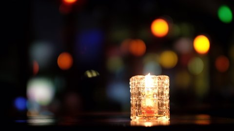 close up a candle light in glass on table. Blur colorful lights in dark background. Bar and restaurant concept