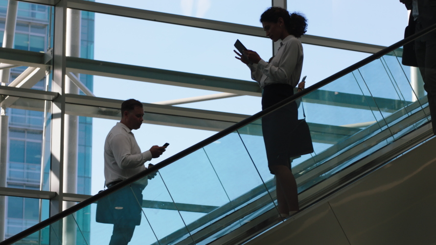 Business people on escalators in busy corporate office lobby working nine to five rush 4k footage   Shutterstock HD Video #1032462428
