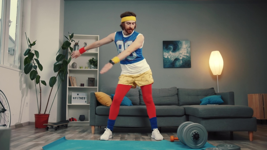 Funny stupid-looking reto fitness man dancing enjoying music and warming up on workout in the living room.   Shutterstock HD Video #1032466298