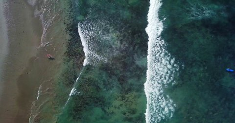 Timelapse. High aerial top view of tiny surfers on sand beach. Small toy figures go into water. Sea waves on beautiful beach aerial view drone shot. Bird's eye view of ocean waves crashing at beach.