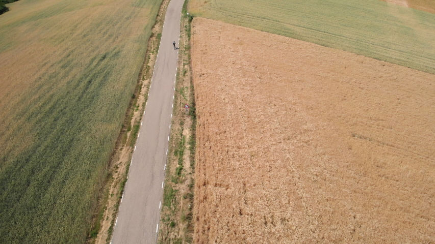 Aerial view of man riding bicycle near Santo Domingo de la Calzada, Spanish town along Way of Saint James. Bike rider on road in Spain seen from drone flying in sky. Biker and sport | Shutterstock HD Video #1032518378