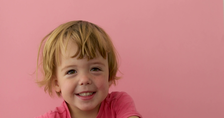 Cute merry light haired kid in bright t-shirt laughing at camera on pink background #1032591578