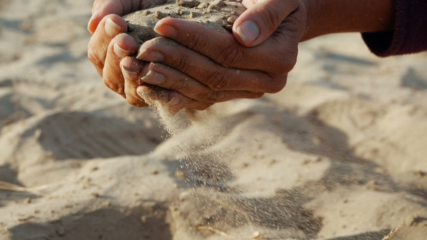 SLOW MOTION, CLOSE UP: The sand passes through the fingers of a young woman. The sand is running through fingers of a lady and is spread by a strong wind. #1032677528
