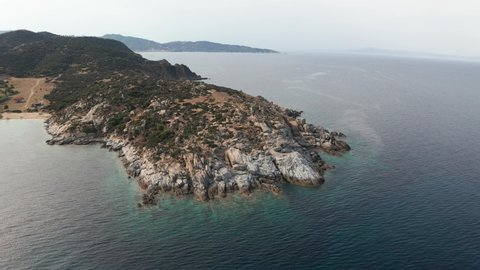 Aerial view of a slide turn from a drone on the view of calm turquoise sea water and rocks from molten lava. Pattern of sea surface and rocky shore. Thracian Sea, Greece. Rocky coast of the peninsula