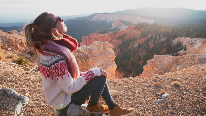 Young woman travels Bryce Canyon national park in Utah, United States, people travel explore nature. Girl hiking in red rock formations | Shutterstock HD Video #1032737498