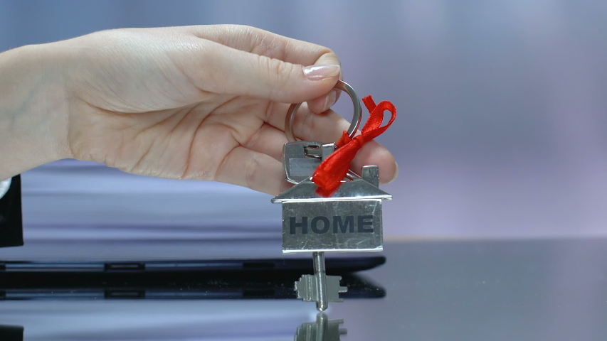 Home word on keychain in woman hand, purchase or long term rental of house