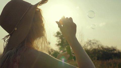 Beautiful Girl Blowing Soap Bubbles.Woman Having Fun.Girl Enjoying At Sunset.Cheerful Blonde Woman Blowing Soap Bubbles.Attractive Woman In Hat Relaxing On Morning Sun In Countryside Field.