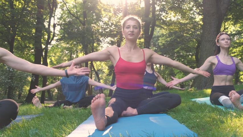 Group of five sporty women practicing yoga lesson with instructor, workout in summer park doing exercise outdoor in meadow. Teamwork, good mood and healthy life concept. | Shutterstock HD Video #1032810968