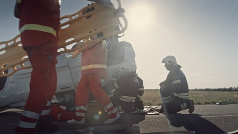 Car Crash Traffic Accident: Paramedics and Firefighters Plan Rescuing Passengers Trapped in a Rollover Vehicle. Medics Prepare First Aid Equipment, Firemen Use Hydraulic Cutters Spreader