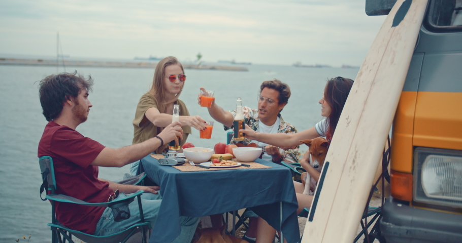 Group of young happy friends enjoying summertime vacation in Europe making cheers while sitting at the dinner table next to a vintage van, beautiful sea view on the background, Slow Motion, Cinematic  | Shutterstock HD Video #1032989318