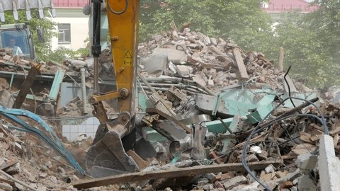 Close-up of bucket Excavator working to get rid of the rubbish in a demolition site. Demolition of the old industrial building.