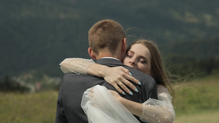 Groom with bride having fun on a mountain hills. Wedding couple. Happy family. Man and woman in love. Lovely groom and bride hugging. Wedding day. Slow motion #1033075688