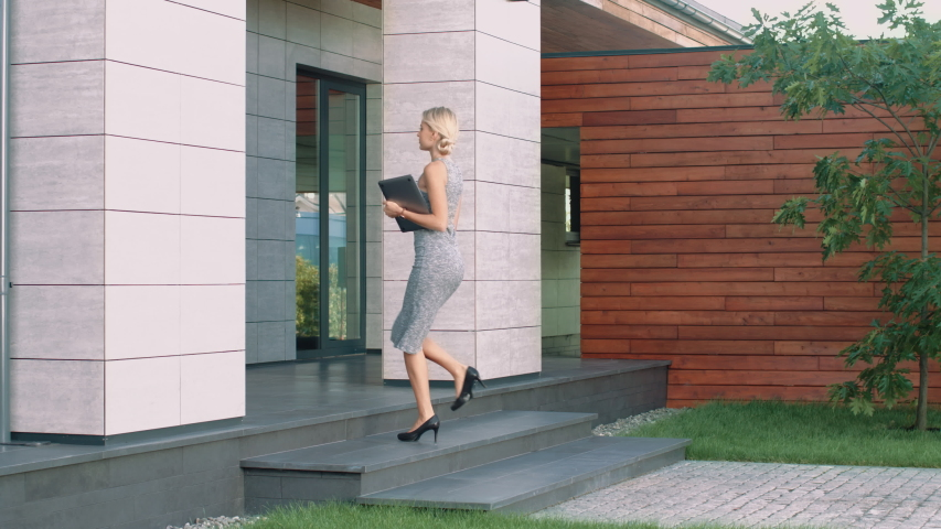Beautiful woman entering business office with laptop. Female employee going up stairs in modern building. Business woman walking up stairs at luxury apartments. Female boss arriving work
