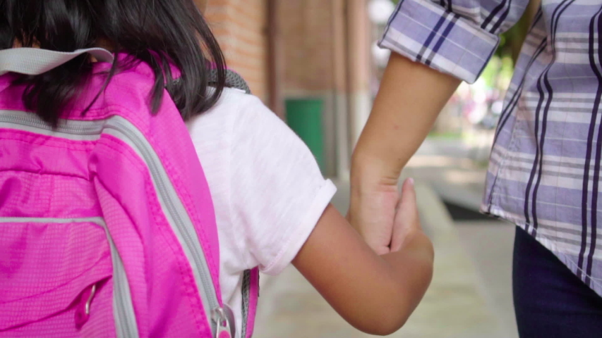 Mother holding hand of little daughter with backpack and walking going to school outdoors. Close up, Back to school concept, Slow motion. | Shutterstock HD Video #1033216868