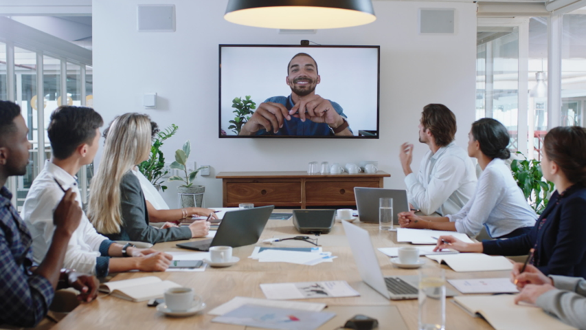 group of business people having conference call meeting in boardroom team leader man chatting to colleagues using online video chat on tv screen discussing ideas in office 4k