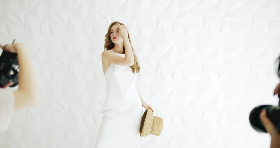 Parallel photoshot of young caucasian female model dressed in white dress, indoors photosession backstage | Shutterstock HD Video #1033300508