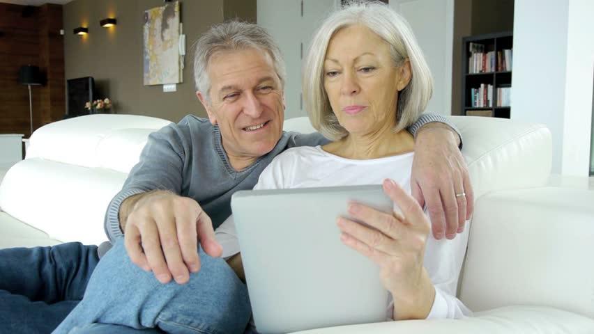 Senior couple in sofa using electronic tab