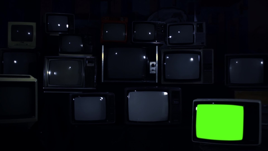 """Pile of Retro TVs from 80s and One TV Turning Off Green Screen. Dark Blue Tone. Zoom Out. You can replace green screen with the footage or picture you want with """"Keying"""" effect. 