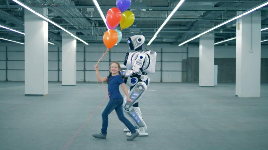 Girl with balloons running near a robot, close up. | Shutterstock HD Video #1033569698