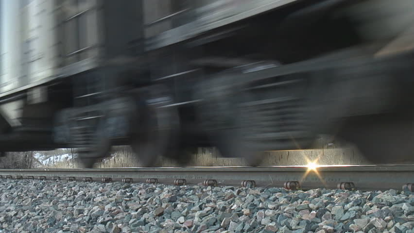 Rail-level tight shot of coal train wheels passing by; HD, audio