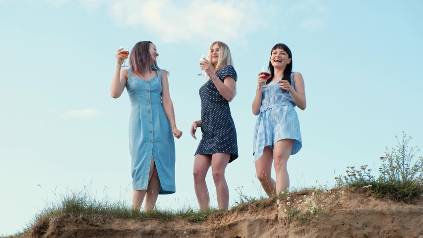 Three young attractive women, in blue dresses are walking along the seashore. Girlfriends communicate, laugh and drink wine. Outdoor recreation. | Shutterstock HD Video #1033706078
