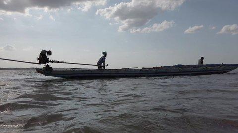 Irukkam Island, Andhra Pradesh / India - July 20 2019: Silhouetted fishermen pushing a wooden boat on a shallow lake